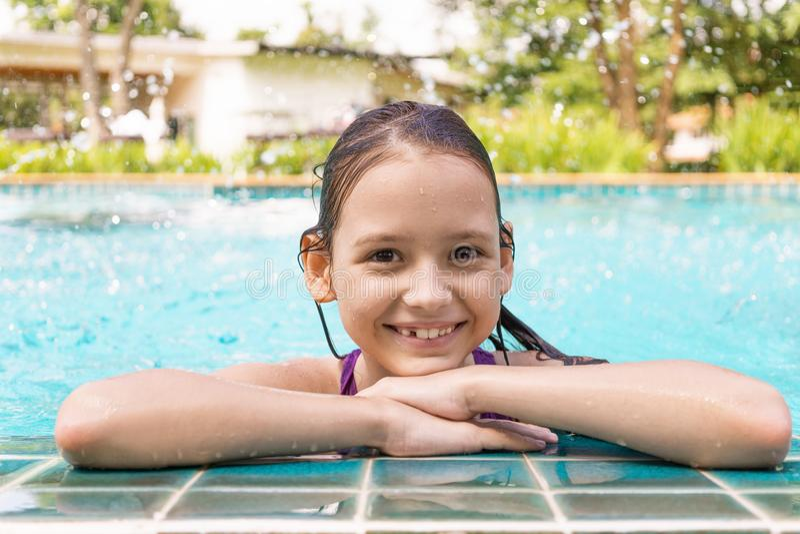 Śliczna uśmiechnięta preteen dziewczyna przy basen krawędzią Podróż, wakacje zdjęcia stock