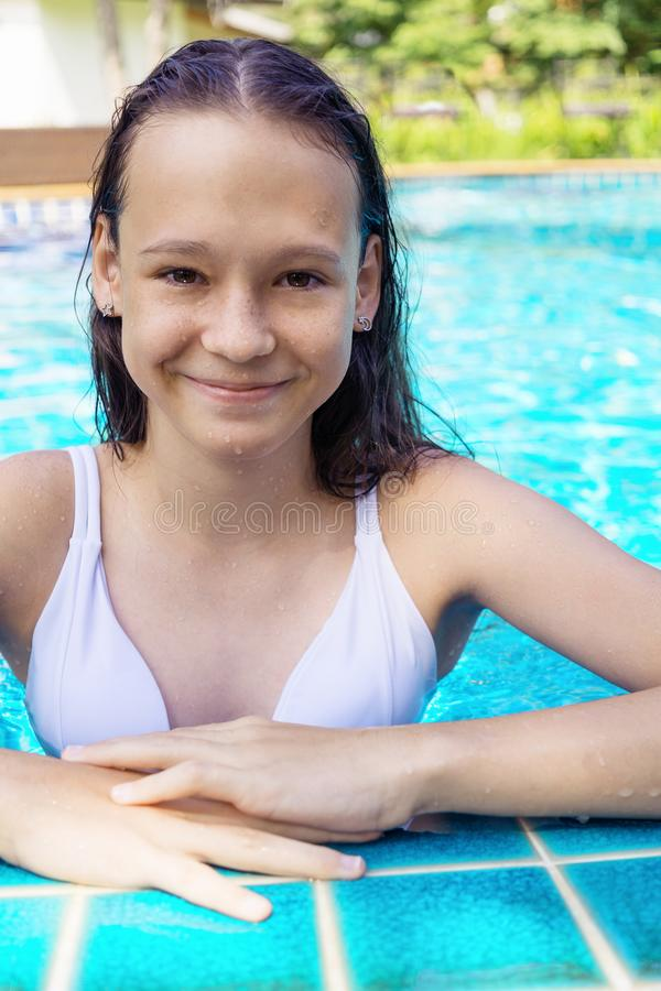 Śliczna uśmiechnięta preteen dziewczyna przy basen krawędzią Podróż, wakacje, dzieciństwo zdjęcia stock