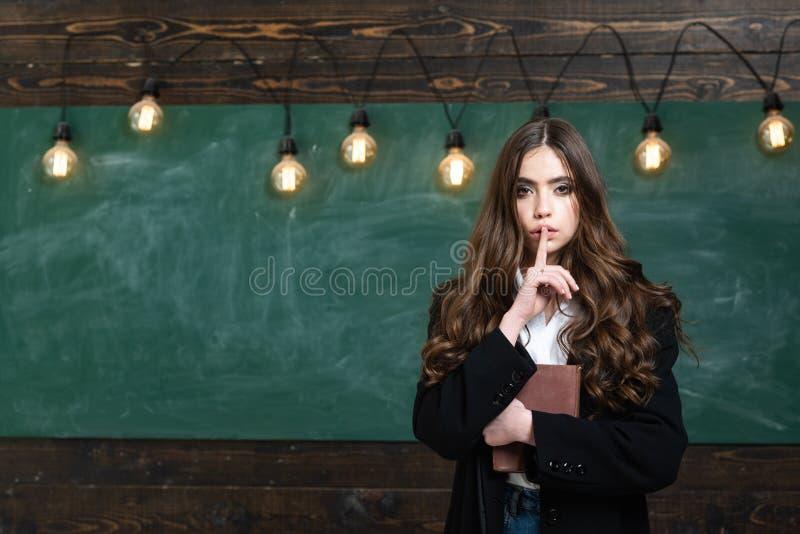 ?liczna uczennica pozuje rozwi?zuj?cy problem na blackboard datowanie Nastolatek szko?a Blondynki kobieta blisko blackboard fotografia royalty free