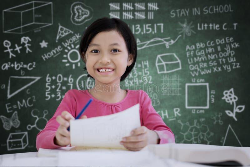 Śliczna uczennica robi notatkom na papierze zdjęcia stock