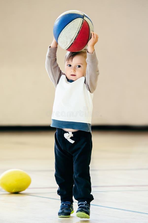 Śliczna urocza mała mała biała Kaukaska dziecko berbecia chłopiec bawić się z balową koszykówką w gym na prostym światła białego  fotografia stock