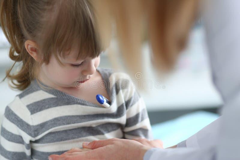 ?liczna zadumana ma?a dziewczynka z termometrem pod jej pach? zdjęcie royalty free