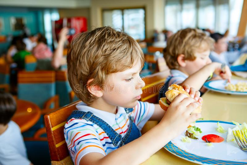 Śliczna zdrowa preschool dzieciaka chłopiec je hamburgeru obsiadanie w szkoły lub pepiniery kawiarni Szczęśliwy dziecko je zdrowy zdjęcie stock