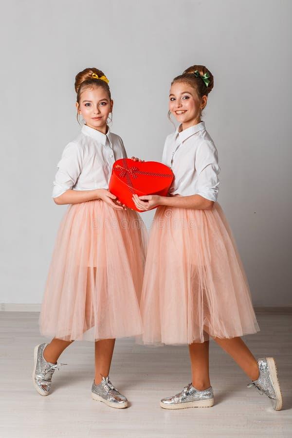 Śliczne bliźniak siostry odpakowywa czerwonego serce kształtowali prezent Odświętności walentynki ` s Świątobliwy dzień pionowo obraz royalty free