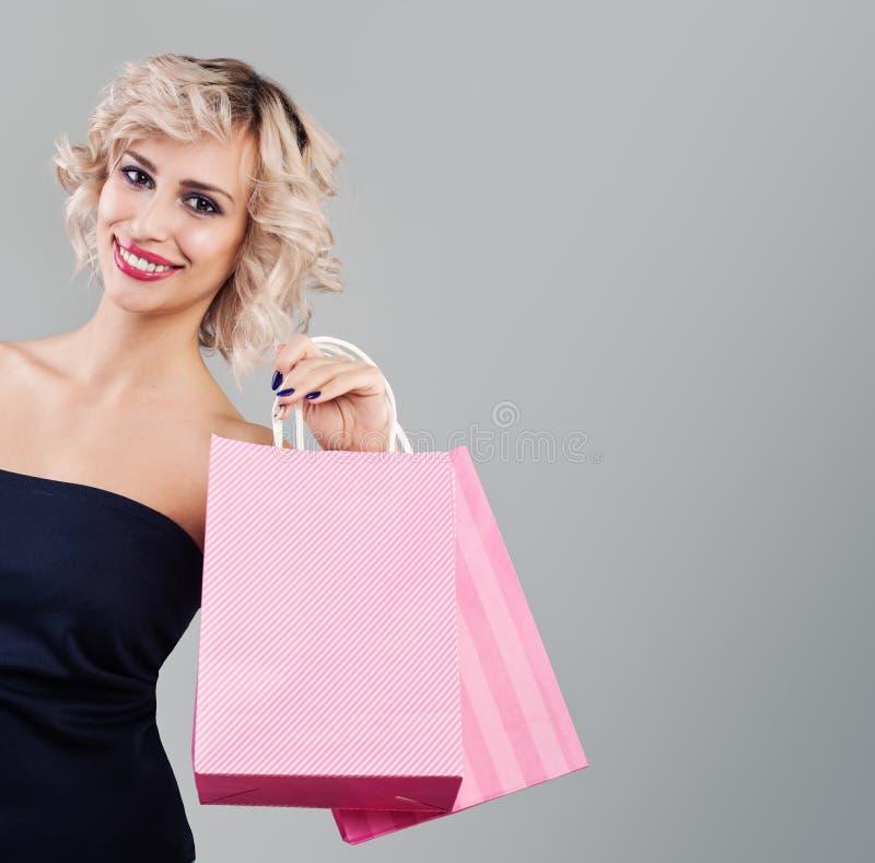 Śliczne blondynki kobiety mienia torby na zakupy na szarym tle zdjęcia stock
