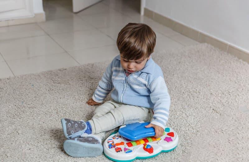 Śliczne chłopiec sztuki z musicalem bawją się w jego pokoju fotografia royalty free