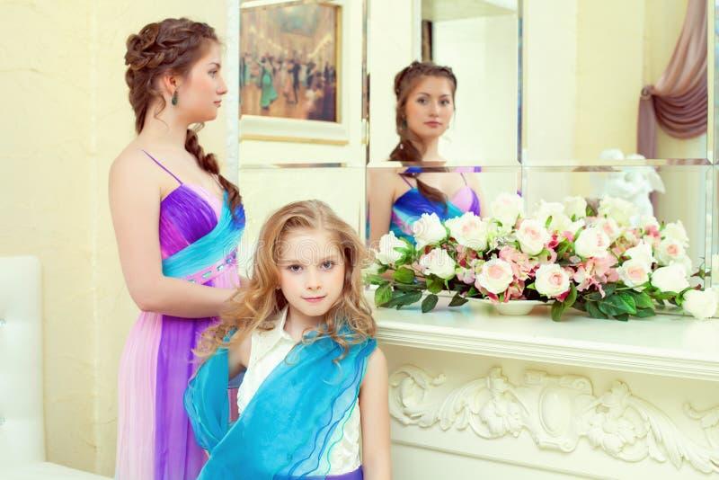Śliczne eleganckie siostry pozuje przed lustrem obrazy royalty free