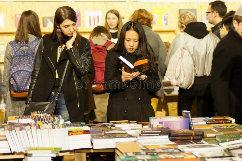 Śliczne kobiety czyta nowe książki w tłumu czytelnicy zdjęcia stock