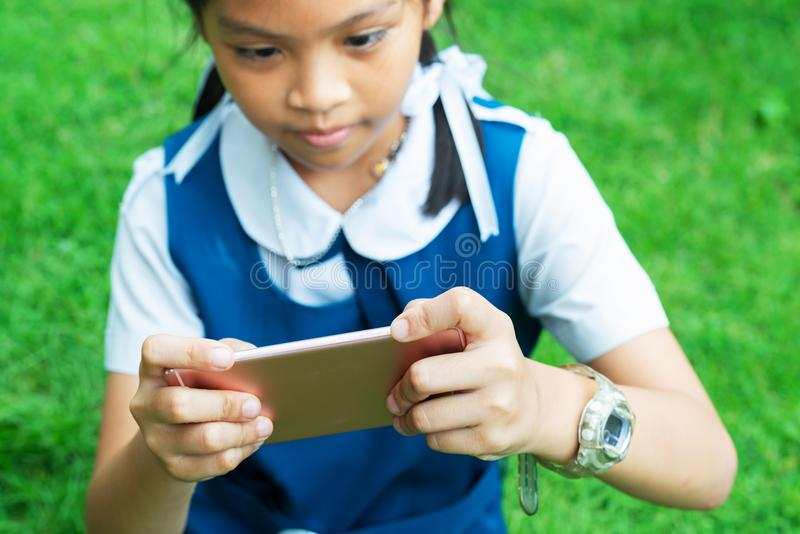 Śliczne małe dziewczynki bawić się internet z mobilnym smartphone na trawie obraz stock