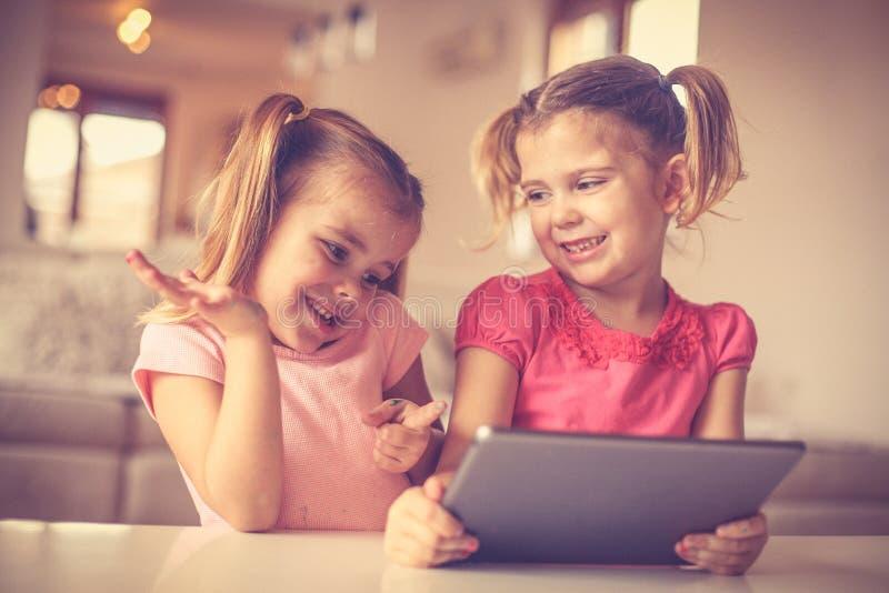 Śliczne małe dziewczynki bawić się na cyfrowej zakładce zdjęcia stock