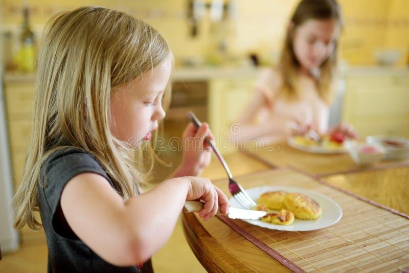 Śliczne małe siostry cieszy się ich śniadanie w domu Ładni dzieci je bliny z truskawkowym kumberlandem przed szkołą obraz royalty free