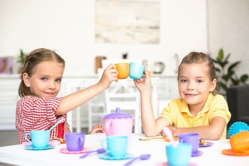 śliczne małe siostry clinking zabawkarskie filiżanki podczas gdy udający mieć herbacianego przyjęcia wpólnie fotografia royalty free