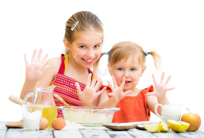 Śliczne małe siostry piec na kuchni obraz royalty free