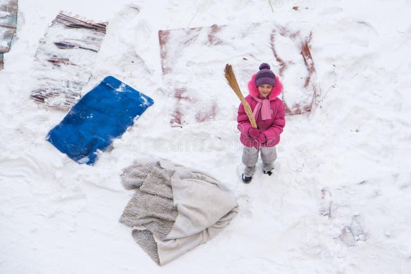 Śliczne małej dziewczynki cleaning maty i dywaniki z miotłą na śnieżnym polu obraz royalty free