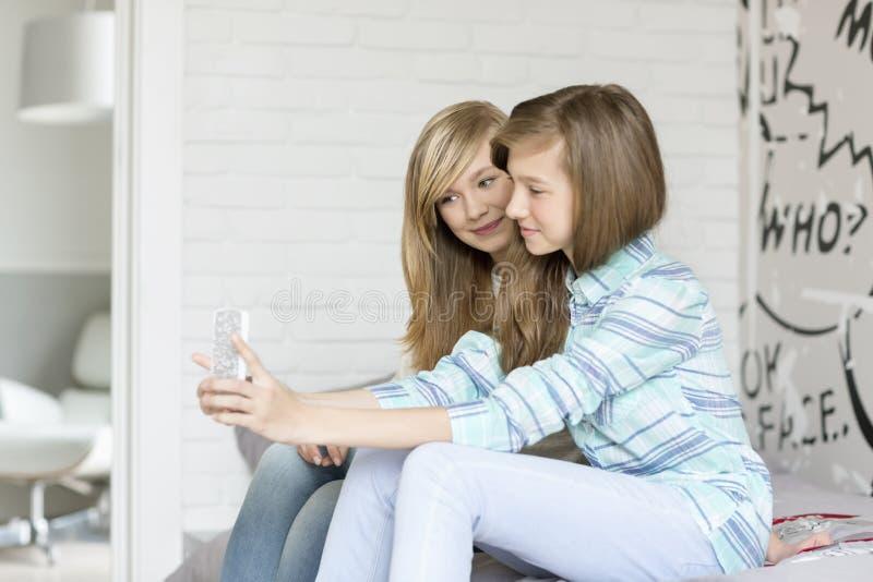 Śliczne siostry ono fotografuje przez telefonu komórkowego w domu fotografia royalty free