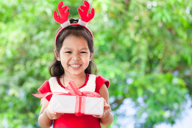 Ślicznego azjatykciego dziecko dziewczyny mienia Bożenarodzeniowy prezent w ręce zdjęcie stock
