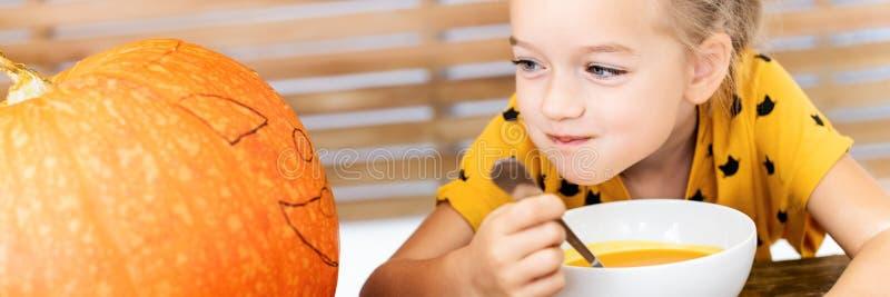 Ślicznego małej dziewczynki łasowania dyniowa polewka i patrzeć wielkiej Halloweenowej bani z zawziętym twarzy wyrażeniem, sztand fotografia royalty free