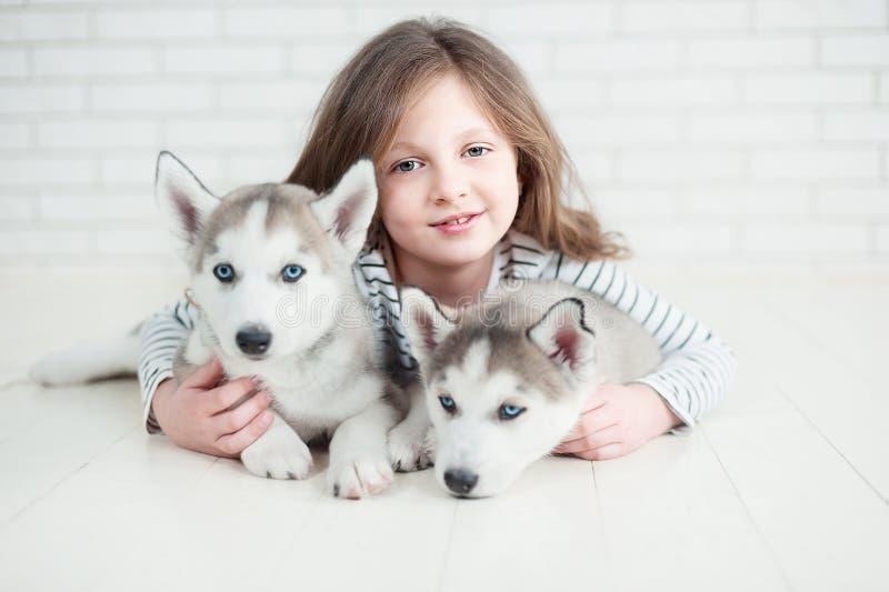 Ślicznego małej dziewczynki przytulenia łuskowaty szczeniak na białym tle obraz royalty free