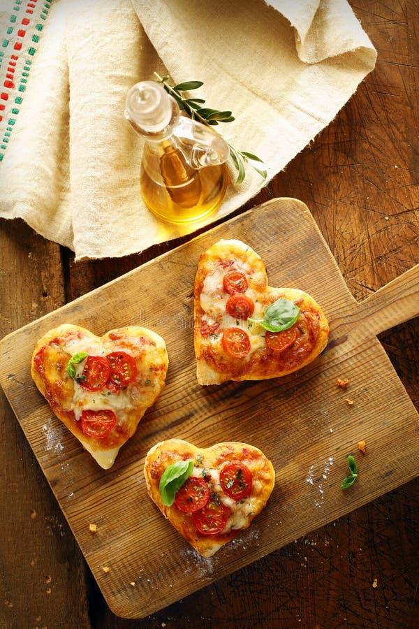 Ślicznego serca kształtne mini pizze zdjęcie stock