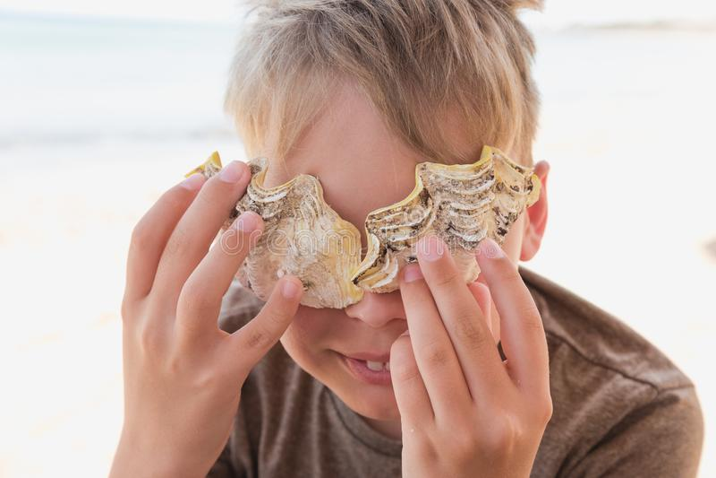 Ślicznego szczęśliwego uśmiechniętego białego dzieciaka mienia żółci seashells blisko przyglądają się uśmiecha się zdjęcie stock
