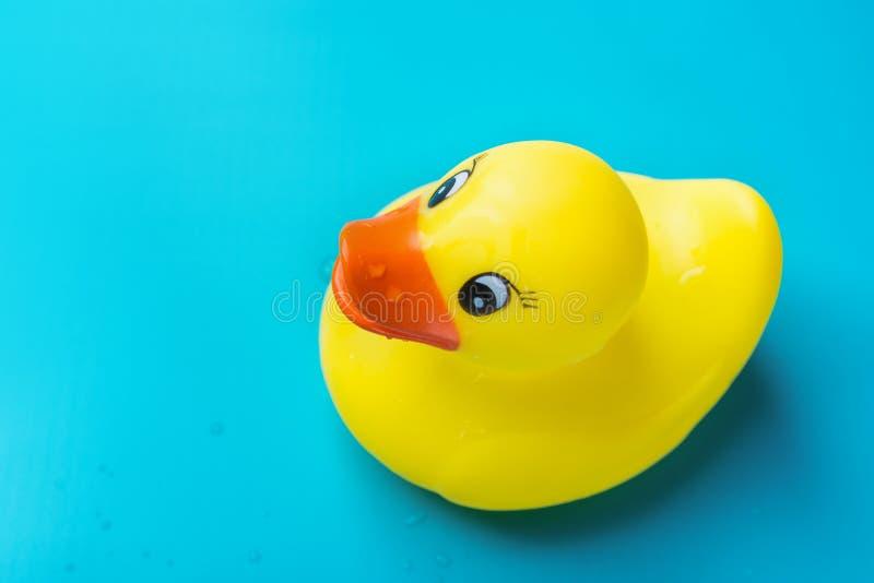 Ślicznego uśmiechniętego koloru żółtego gumy skąpania mokra kaczka z wodą opuszcza na błękitnym tle Berbecia munchkin zabawki Żar fotografia royalty free