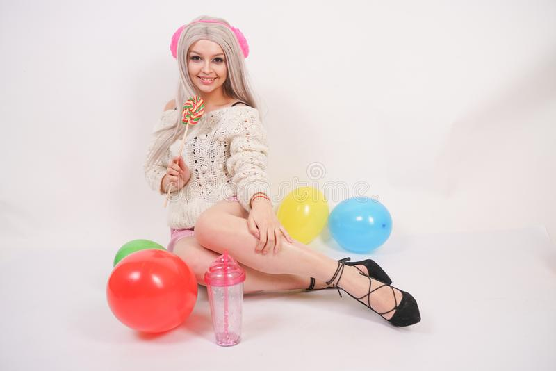 Ślicznej blondynki caucasian szczęśliwa dziewczyna ubierał w milky kolor dziającym pulowerze i śmieszni skróty, siedzi na biały p obraz stock