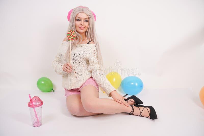 Ślicznej blondynki caucasian szczęśliwa dziewczyna ubierał w milky kolor dziającym pulowerze i śmieszni skróty, siedzi na biały p zdjęcie stock