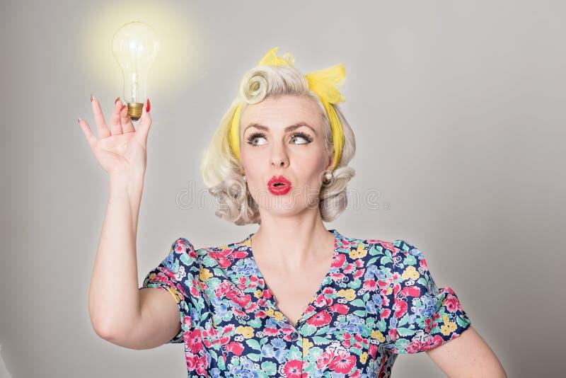 Ślicznej blondynki retro dziewczyna trzyma rozjarzoną żarówkę - humorystyczny przeciw fotografia stock