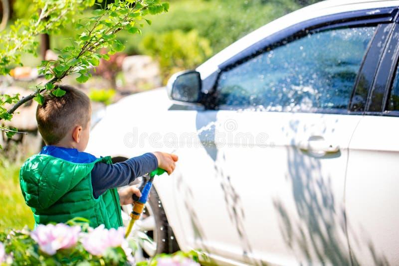 Ślicznej chłopiec płuczkowy samochód outdoors obraz royalty free
