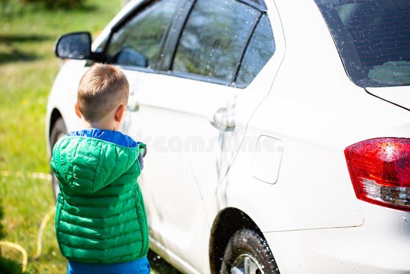 Ślicznej chłopiec płuczkowy samochód outdoors zdjęcie royalty free