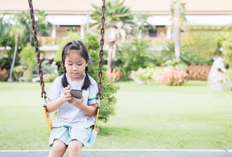 Ślicznej dziewczyna ucznia sztuki mądrze telefon na huśtawce obraz stock