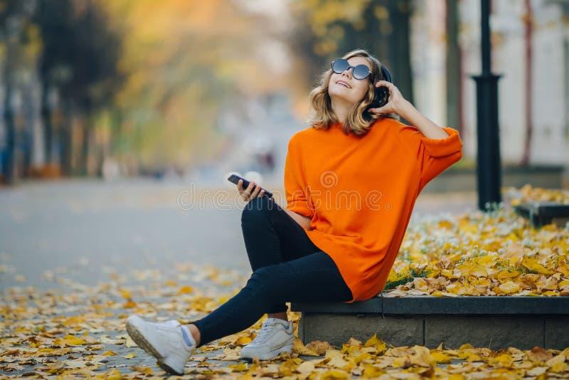 Ślicznej młodej dziewczyny słuchająca muzyka w hełmofonach, miastowy styl, eleganckiego modnisia nastoletni obsiadanie na chodnic obraz royalty free
