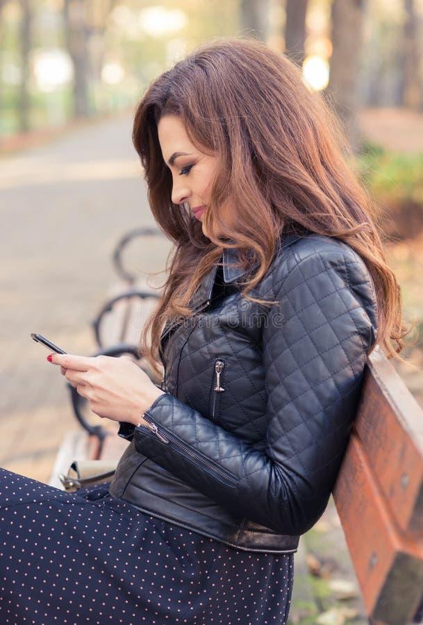 Ślicznej młodej kobiety texting wiadomości na telefonie komórkowym obraz royalty free