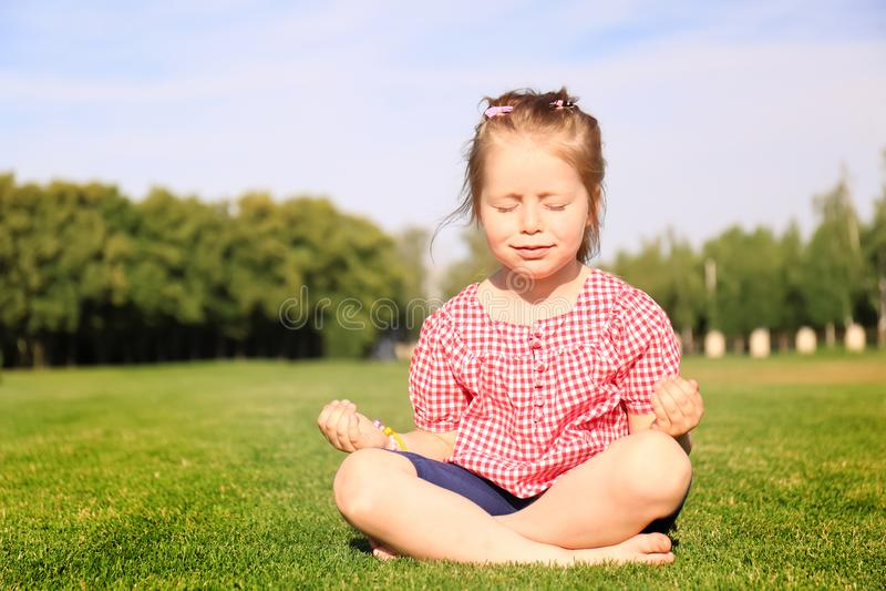 Ślicznej małej dziewczynki ćwiczy joga w parku na słonecznym dniu fotografia royalty free