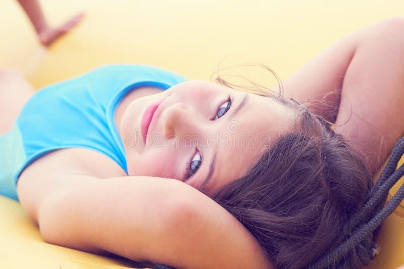 Ślicznej małej dziewczynki relaksujący lying on the beach na nadmuchiwanej materac w górę portreta fotografia stock