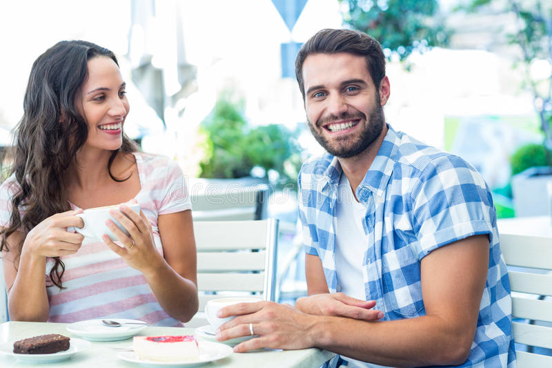 Ślicznej pary siedzący outside przy kawiarnią z mężczyzna ono uśmiecha się przy kamerą fotografia royalty free