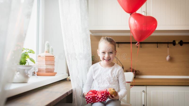 Ślicznej preschooler dziewczyny odświętności 6th urodziny Dziewczyna trzyma jej urodzinową babeczkę pięknie zawijającą teraźniejs obraz royalty free