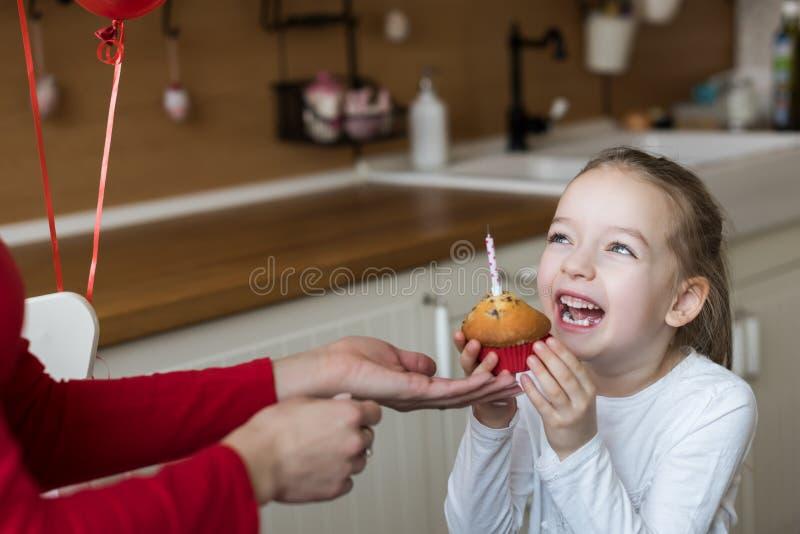 Ślicznej preschooler dziewczyny odświętności 6th urodziny Macierzysta daje córka urodzinowa babeczka z świeczką partyjni urodzino obraz royalty free