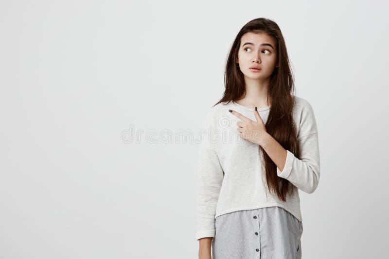 Ślicznej rozochoconej brunetki młoda kobieta wskazuje z palcem wskazującym oddalonym, pokazuje coś ciekawego i ekscytuje dalej, obrazy stock