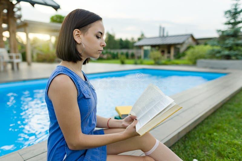 Ślicznej studenckiej dziewczyny czytelnicza książka, tło pływacki basen, gazon blisko domu Edukacja, lato, wiedza obraz royalty free