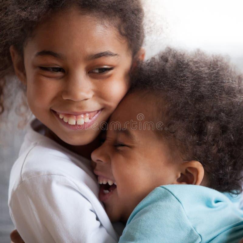 Śliczni amerykanin afrykańskiego pochodzenia dzieciaki ściska śmiać się z śmiesznymi twarzami, cl obraz royalty free