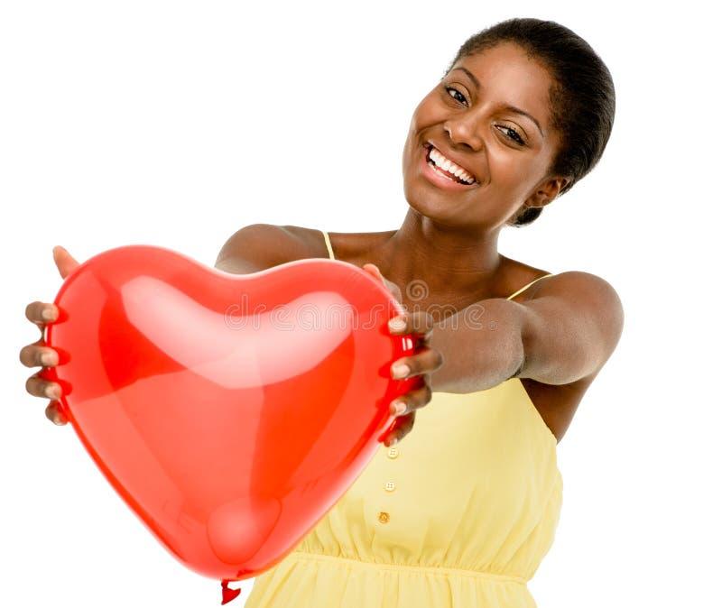 Śliczni amerykanin afrykańskiego pochodzenia kobiety mienia czerwieni balonu serca valentines obraz royalty free