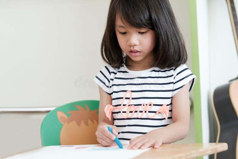 Śliczni azjatykci dziewczyna rysunkowego koloru ołówki w dzieciniec sala lekcyjnej, zdjęcia stock