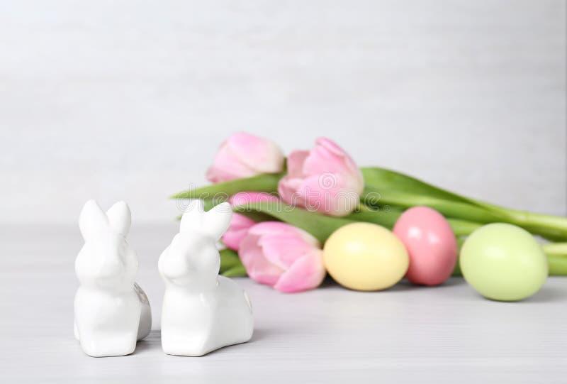 Śliczni ceramiczni króliki, Wielkanocni jajka i wiosna tulipany na stole przeciw lekkiemu tłu, fotografia royalty free