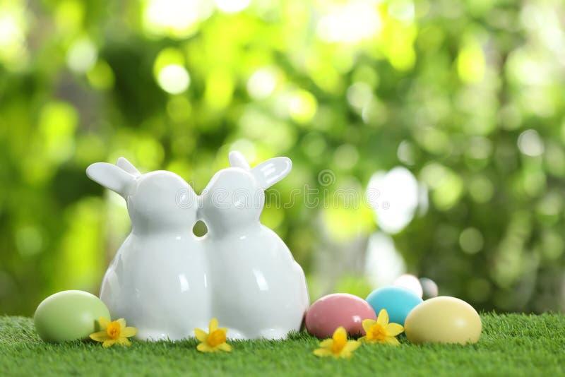 Śliczni ceramiczni Wielkanocni króliki i farbujący jajka na zielonej trawie przeciw zamazanemu tłu zdjęcie stock