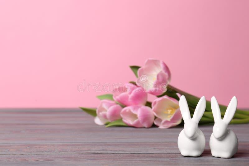 Śliczni ceramiczni Wielkanocni króliki i wiosna tulipany na stole przeciw koloru tłu, przestrzeń dla teksta zdjęcie stock
