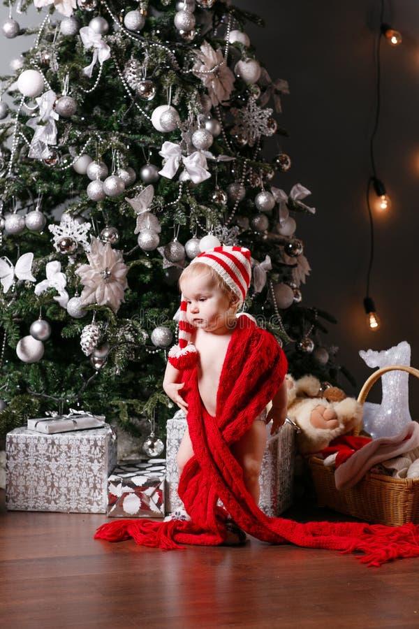 Śliczni chłopiec i bożych narodzeń prezenty Małe dziecko ma zabawę blisko choinki w żywym pokoju Kochający rodzinny syn Wesoło obrazy stock