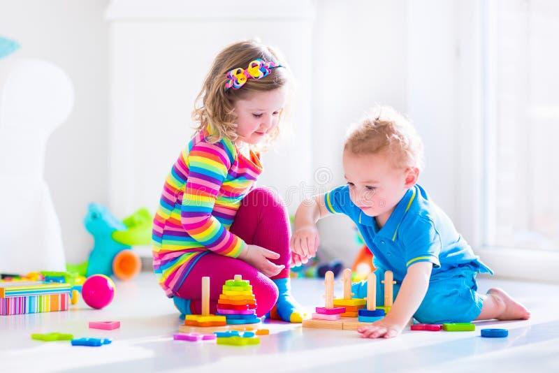 Śliczni dzieci bawić się z drewnianymi zabawkami fotografia royalty free