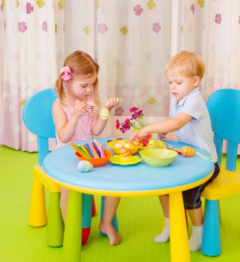 Śliczni dzieci malują Wielkanocnych jajka zdjęcia royalty free