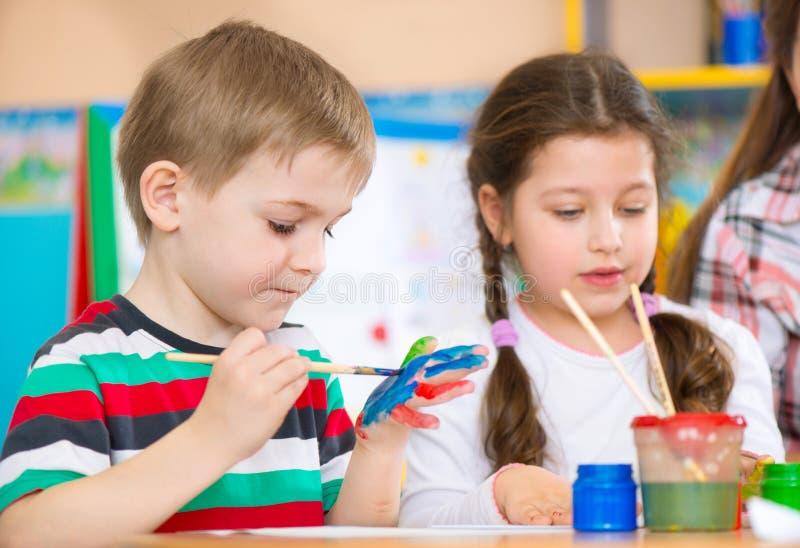 Śliczni dzieci maluje przy dziecinem zdjęcie royalty free
